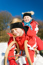 Sisters in snow on toboggan Royalty Free Stock Images