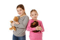 Sisters with teddybears two girls hugging and smiling isolated Stock Image