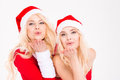 Sisters twins in santa claus clothes and hats sending kisses Royalty Free Stock Photo