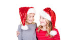 Sisters or two young girls wearing santa hats looking at each other on an isolated white background Royalty Free Stock Image