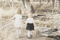 Sisters walk in a wooded area holding hands cute outfits Royalty Free Stock Photo