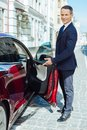 Delighted good looking man inviting to sit into his car Royalty Free Stock Photo