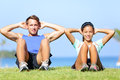 Sit ups fitness couple exercising sit up outside in grass in summer fit happy people working out cross training beautiful young Stock Image