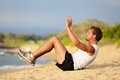 Sit ups fitness crossfit man doing situps on beach training and working out with high impact fit male model in intense Stock Image