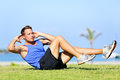 Sit ups fitness man exercising sit up outside in grass in summer fit male athlete working out cross training in summer caucasian Royalty Free Stock Photos