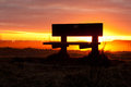 Sit and wait beachside bench against the sunset Stock Photos