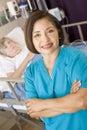 Sitio del doctor Standing In Her Patients Imagen de archivo libre de regalías