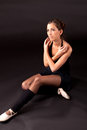 Sitting ballerina in black ballet tutu on black background with extended leg and looking up Stock Photo