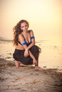 Sitting beauty woman on the beach at sunset Royalty Free Stock Photos