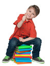 Sitting on the books cheerful boy a smiling young is pile of and holds his thumb up Royalty Free Stock Photography