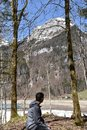 A sitting boy between conifer trees observing Klöntalersee lake in early spring sunny day in Klöntal Royalty Free Stock Photo