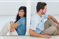 Sitting couple are separated by wall with women looking at camera Stock Photo