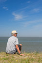 Sitting on dutch dyke elderly man is in lauwersoog Stock Photos
