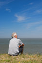 Sitting on dutch dyke elderly man is in lauwersoog Royalty Free Stock Photography