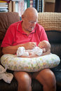 Sitting grandpa s lap baby laying in his grandfather grandfather is talking and grandson is looking at him Stock Images