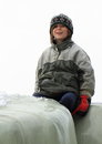 Sitting little boy with soft smile in winter clothes Royalty Free Stock Photography