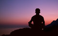 Sitting man silhouette in meditation pose on the top of hill Stock Photo