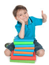 Sitting near the books cheerful boy a smiling young is pile of and holds his thumb up Royalty Free Stock Photography