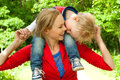 Sitting ons mommys neck happy mother and son having a nice day in the park Royalty Free Stock Photo