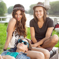 Sitting on park bench three happy young people together outdoors Royalty Free Stock Photo