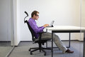 Sitting posture at tablet tired business man on chair in his office Stock Photography