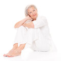 Sitting senior woman in front of white background Stock Image