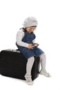 Sitting on a suitcase girl playing with phone over white background Stock Images