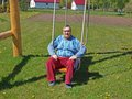 Sitting on swing elderly country farmer the Royalty Free Stock Images