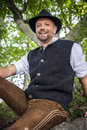 Sitting traditional bavarian man with costume is in a forest Stock Photography