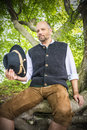 Sitting traditional bavarian man with costume is in a forest Stock Images