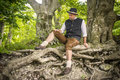 Sitting traditional bavarian man with costume is in a forest Royalty Free Stock Photos