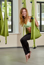 Sitting woman in anti gravity aerial yoga portrait young posing green hammock indoor fitness club Royalty Free Stock Image