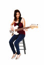 Sitting woman playing guitar a young on a chair her isolated on white background Stock Image