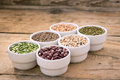 Six bowls with cereals on wooden desk bean pea lentil haricot kidney Stock Photos