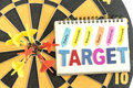 Six dart in bullseye with words target on the notebook with hand Royalty Free Stock Photo