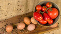 Six eggs with decorative pepper and a cup with red tomatoes on a wooden surface and canvas Royalty Free Stock Photo