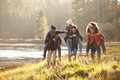Six friends have fun piggybacking in the countryside by lake Royalty Free Stock Photo