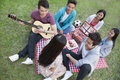 Six friends having a picnic and hanging out in the park playing guitar and talking Royalty Free Stock Photography