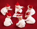 Six little santa helpers are examining christmas gift Royalty Free Stock Photo