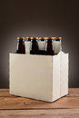 Six pack beer on wood table closeup of a of brown bottles a rustic wooden vertical format with a light to dark gray spot Royalty Free Stock Photography