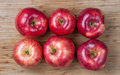 Six red apples on a wood cutting board Stock Photography