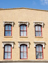 Six red windows in an old brown brick building under blue skies Stock Photography