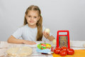 Six-year girl sitting at kitchen table in front of her are vegetables, base and other ingredients for pizza Royalty Free Stock Photo