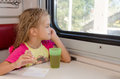 Six-year girl sitting on train at the table on outboard second-class carriage and enthusiastically looking out the window