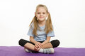 Six year old girl athlete sitting on a rug Royalty Free Stock Photo