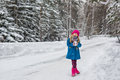 Six year old girl in a blue coat and a pink hat and boots grimacing in the winter forest Royalty Free Stock Photo