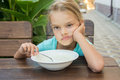 Six year old girl does not want to eat porridge for breakfast sitting at a table with a sour face and did Royalty Free Stock Photography