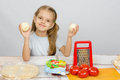 Six year old girl at kitchen table having fun holding vegetables Royalty Free Stock Photo