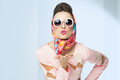 Sixties style girl blowing a kiss retro fashion with silk scarf and sunglasses Stock Images