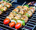 Sizzling barbecue sticks Stock Photography